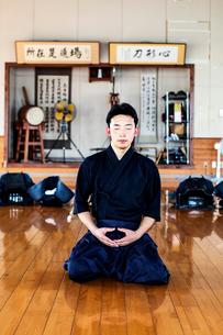 Male Japanese Kendo fighter kneeling on wooden floor, meditating.の写真素材 [FYI02265395]