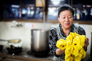 Japanese woman standing in a textile plant dye workshop, holding piece of bright yellow fabric.の写真素材 [FYI02265396]
