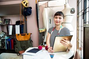 Japanese female fashion designer working in her studio, smiling at camera.の写真素材 [FYI02265397]