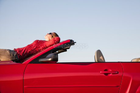 A Caucasian woman resting on the hood of her convertible sports car at a rest stop.の写真素材 [FYI02265399]