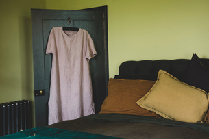 Interior view of bedroom with light green walls, double bed with and pale pink linen nightgown on haの写真素材 [FYI02265407]