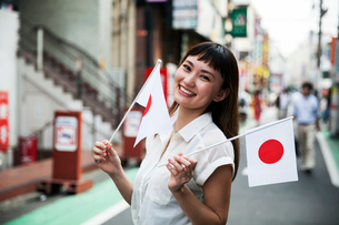 Smiling Japanese woman with long brown hair wearing white short-sleeved blouse standing in a street,の写真素材 [FYI02265417]