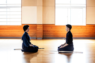 Female and male Japanese Kendo fighters kneeling opposite each other on wooden floor.の写真素材 [FYI02265419]