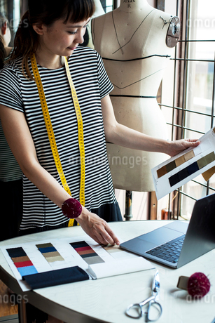 Japanese female fashion designer working in her studio, looking at fabric samples, using laptop.の写真素材 [FYI02265420]
