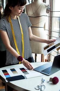 Japanese female fashion designer working in her studio, looking at fabric samples, using laptop.の写真素材 [FYI02265420]