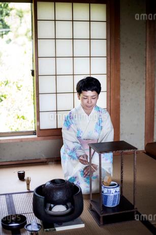Japanese woman wearing traditional white kimono with blue floral pattern kneeling on tatami mat duriの写真素材 [FYI02265426]