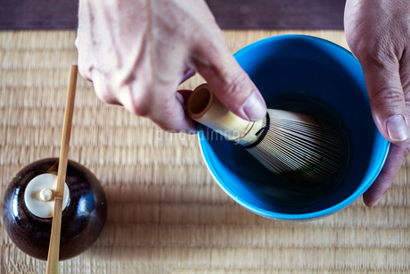 High angle close up of person using bamboo whisk to prepare Matcha tea in a blue bowl during tea cerの写真素材 [FYI02265431]