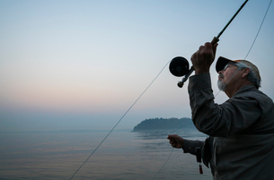 Senior Caucasian male fly fishing for salmon and sea run cutthroat trout off the coastの写真素材 [FYI02265438]