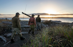Two fly fisherman and a guide walk to a salt water beach at sunrise to fish for searun coastal cutthの写真素材 [FYI02265442]