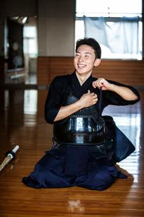 Male Japanese Kendo fighter kneeling on floor, fastening his breastplate.の写真素材 [FYI02265448]