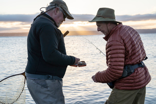 A male fly fisherman watches his guide work putting on a new fly to try for salmon or trout at a salの写真素材 [FYI02265451]