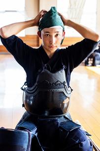 Male Japanese Kendo fighter kneeling on floor, wearing breastplate and tying headscarf, looking at cの写真素材 [FYI02265461]