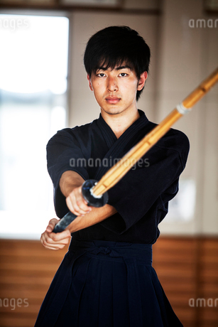 Male Japanese Kendo fighter holding wood sword in combat pose, looking at camera.の写真素材 [FYI02265463]