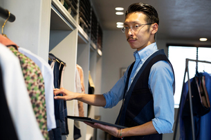 Japanese salesman with moustache wearing glasses standing in clothing store, looking at clothes on aの写真素材 [FYI02265468]