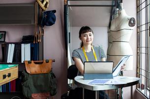 Japanese female fashion designer working in her studio, smiling at camera.の写真素材 [FYI02265469]