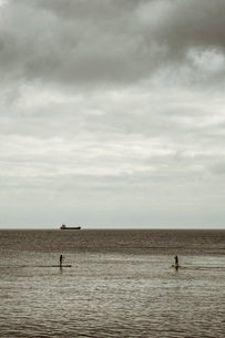 View out to sea from the cliffs, two people paddle boarding on a calm sea, and a large freight tankeの写真素材 [FYI02265475]