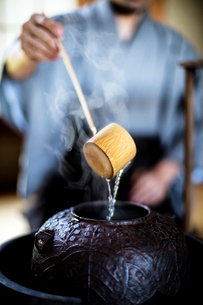 Close up of traditional Japanese Tea Ceremony, man using a Hishaku, a bamboo ladle, to pour hot wateの写真素材 [FYI02265479]