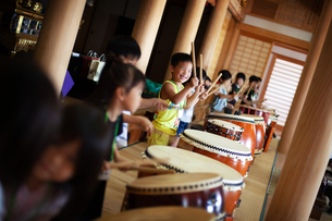 Group of children playing the drums in a temple, a traditional set of drums.の写真素材 [FYI02265485]