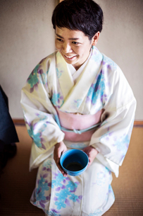 Japanese woman wearing traditional white kimono with blue floral pattern kneeling on floor during teの写真素材 [FYI02265491]
