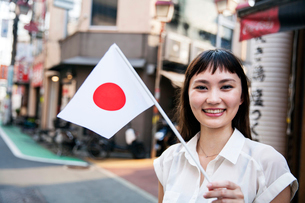 Smiling Japanese woman with long brown hair wearing white short-sleeved blouse standing in a street,の写真素材 [FYI02265496]