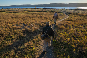 Two fly fisherman walking a well worn trail to a salt water beach on Indian Island in northwest Washの写真素材 [FYI02265501]
