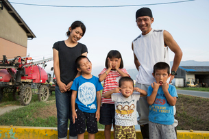 Portrait of smiling Japanese farmer, his wife and four children standing in their yard, children pulの写真素材 [FYI02265508]