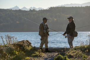 Two fly fisherman talk over techniques for fishing while standing on a salt water beach in northwestの写真素材 [FYI02265513]