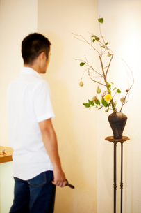 Japanese man standing in flower gallery, looking at Ikebana arrangement in brown vase.の写真素材 [FYI02265516]