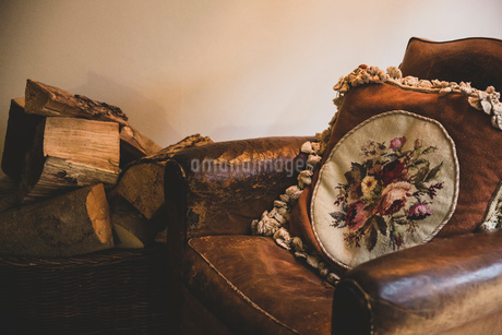 Basket of firewood next to vintage tan leather armchair with embroidered cushion with floral patternの写真素材 [FYI02265521]