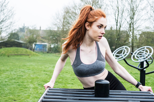 Young woman with long red hair wearing sports kit, using outdoor exercise machine.の写真素材 [FYI02265522]