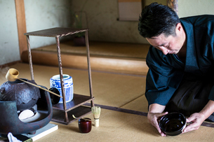 Japanese man wearing traditional kimono kneeling on floor, holding tea bowl, during tea ceremony.の写真素材 [FYI02265526]
