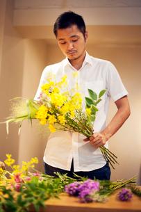 Japanese man in a flower gallery, working on Ikebana arrangement.の写真素材 [FYI02265534]