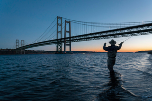 Silhouette of fly fisherman casting for salmon and searun cutthroat trout at sunsetの写真素材 [FYI02265540]