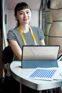 Japanese female fashion designer working in her studio, smiling at camera.の写真素材 [FYI02265541]