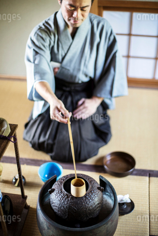 Traditional Japanese Tea Ceremony, man wearing kimono sitting on floor, using a Hishaku, a bamboo laの写真素材 [FYI02265544]