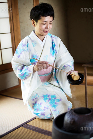 Japanese woman wearing traditional white kimono with blue floral pattern kneeling on tatami mat duriの写真素材 [FYI02265546]