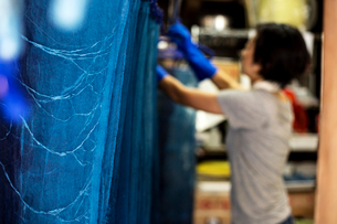 Japanese woman standing in a textile plant dye workshop, hanging up freshly dyed bright blue fabric.の写真素材 [FYI02265551]