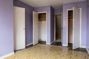 Interior view of empty bedroom with yellow floor and lilac walls in abandoned house, white wardrobeの写真素材 [FYI02265558]
