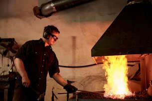 An artisan metal worker heating metal in a forge in his workshop.の写真素材 [FYI02265572]