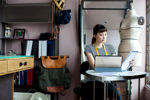 Japanese female fashion designer working in her studio, sitting at table, looking at fabric samples.の写真素材 [FYI02265576]