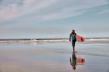 Man holding a surf board walking out to the sea at low tide.の写真素材 [FYI02265582]
