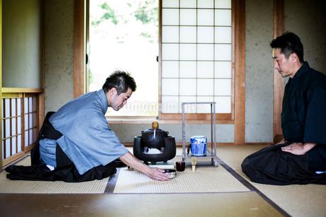 Two Japanese men wearing traditional kimonos kneeling on floor during tea ceremony.の写真素材 [FYI02265586]