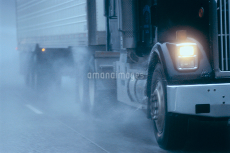 Partial view of large commercial truck driving in hazardous conditions of snow and rain on a freewayの写真素材 [FYI02265589]