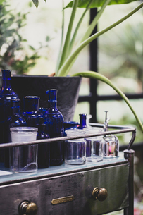 Close up of clear and blue glass jars and bottles on vintage metal table with drawer.の写真素材 [FYI02265592]