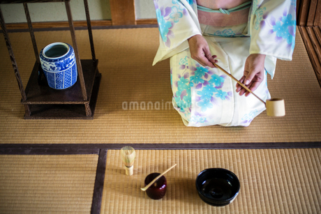High angle view of Japanese woman wearing traditional white kimono with blue floral pattern kneelingの写真素材 [FYI02265595]
