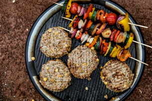 Food on a barbeque, vegetable kebabs and home made burgers, cooking outdoors.の写真素材 [FYI02265603]