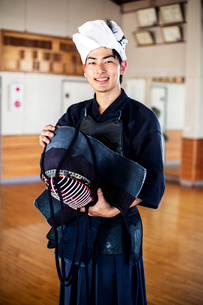 Male Japanese Kendo fighter standing in a gym, holding Kendo mask, looking at camera.の写真素材 [FYI02265606]