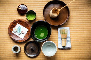 Tea ceremony utensils including bowl of green Matcha tea, a bamboo whisk and Wagashi sweets.の写真素材 [FYI02265609]