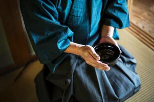 High angle close up of Japanese man wearing kimono holding tea bowl during tea ceremony.の写真素材 [FYI02265614]
