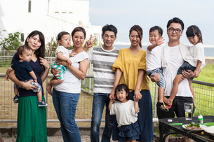 Group portrait of Japanese families with young children standing in a back garden, smiling at cameraの写真素材 [FYI02265640]